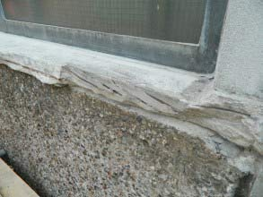 Spalled concrete window sill
